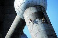 8月13日,上海陆家嘴,两名工人在高空给东方明珠做柱体清洗。