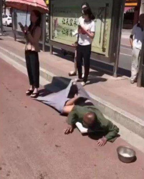 乞丐美女美女柔术酷优乞讨发生,被裤子踩到残疾,随后爬行的图片