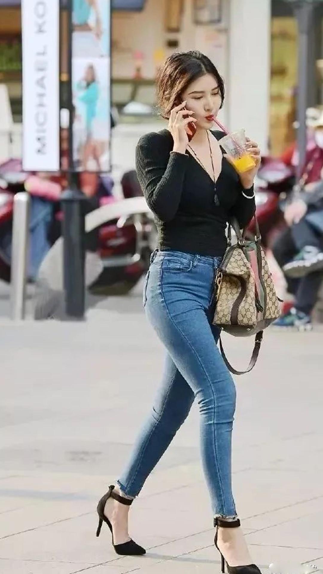 <b>路人街拍:喝着天天果汁的美女,身穿修身牛仔裤,尽显婀娜身材</b>