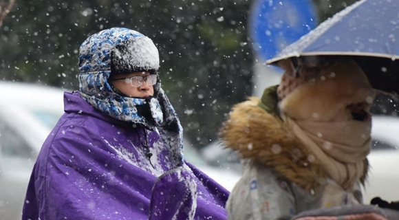 全国多地迎降雪 民众出行秒变雪人